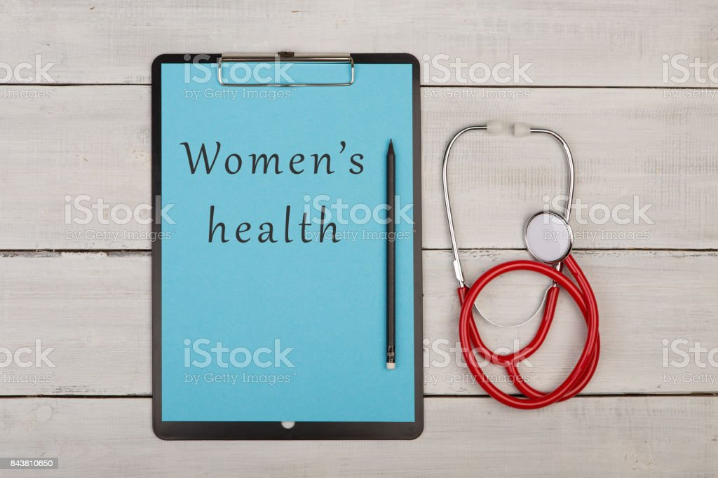 clipboard with text 'Women's health', stethoscope stock photo