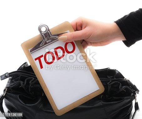 Mature woman with nude color stiletto nails holds clipboard with text above her handbag
