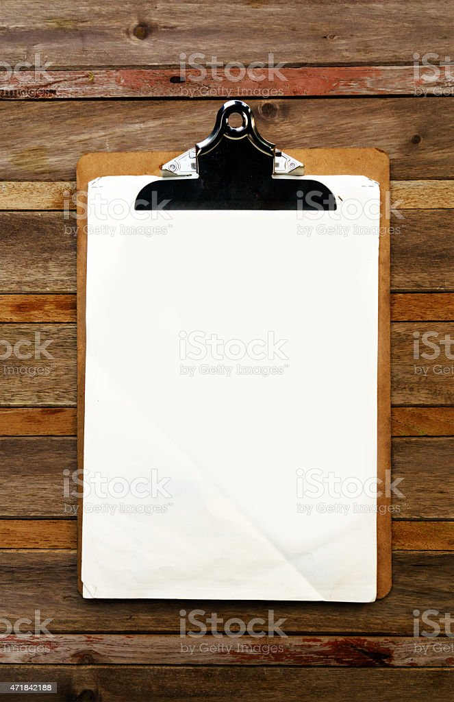 Clipboard with white paper hanging from a wooden wall stock photo