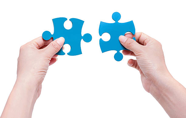 frau setzen gemeinsam puzzle stücke - dinge die zusammenpassen stock-fotos und bilder