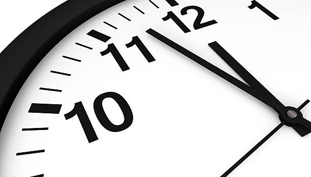 Clock Almost Midnight Close-up face view of an analogic wall clock showing almost midnight hour. midnight stock pictures, royalty-free photos & images
