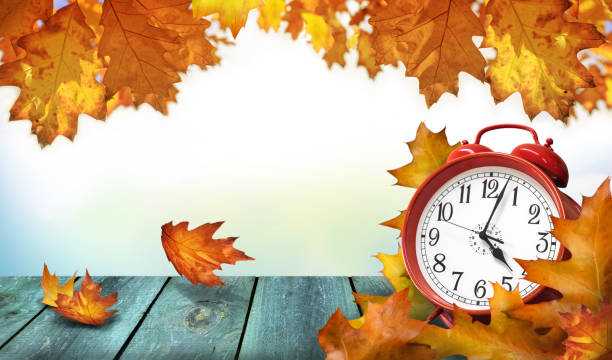Clock and autumn leaves on the wooden table - daylight saving time concept Clock and autumn leaves on the wooden table - daylight saving time concept daylight savings stock pictures, royalty-free photos & images