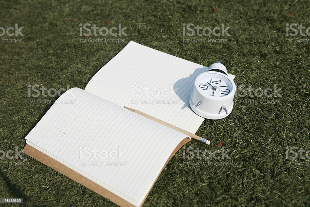 clock and book on grass royalty-free stock photo