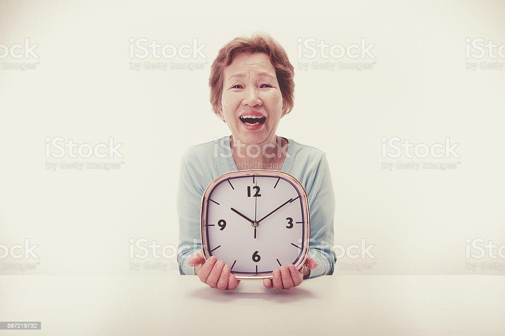 Clock and elderly women stock photo