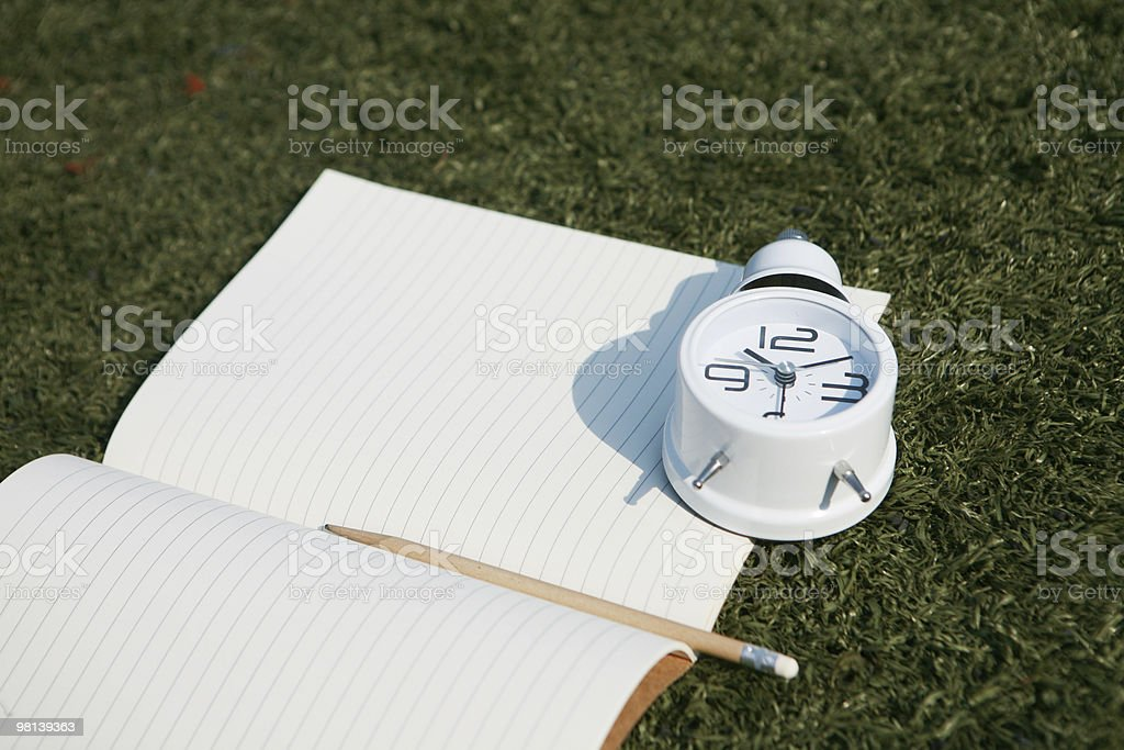 clock and notebook on grass royalty-free stock photo