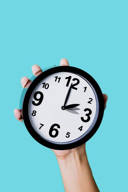 clock being adjusted backward or forward stock photo