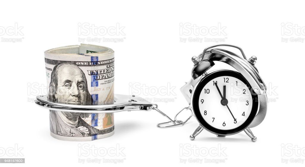Clock connected by handcuffs with money on white. stock photo