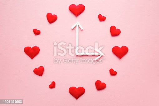 1139289535 istock photo Clock created from bright red hearts and white arrows on light pink table background. Dating time. Love concept. Close up. Flat lay. Top down view. 1201454590