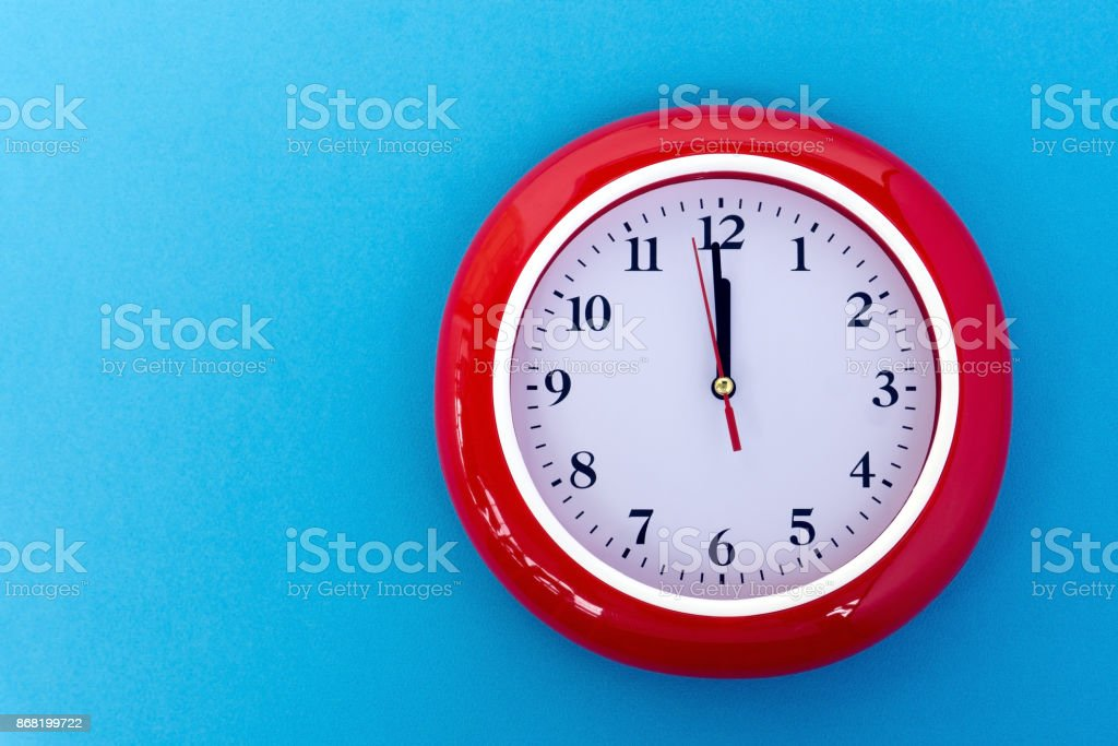 Clock Face Pointing at 12 O'Clock on Blue Background stock photo