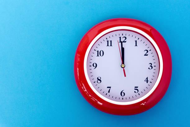 reloj cara apuntando a 12:00 sobre fondo azul - wall clock fotografías e imágenes de stock