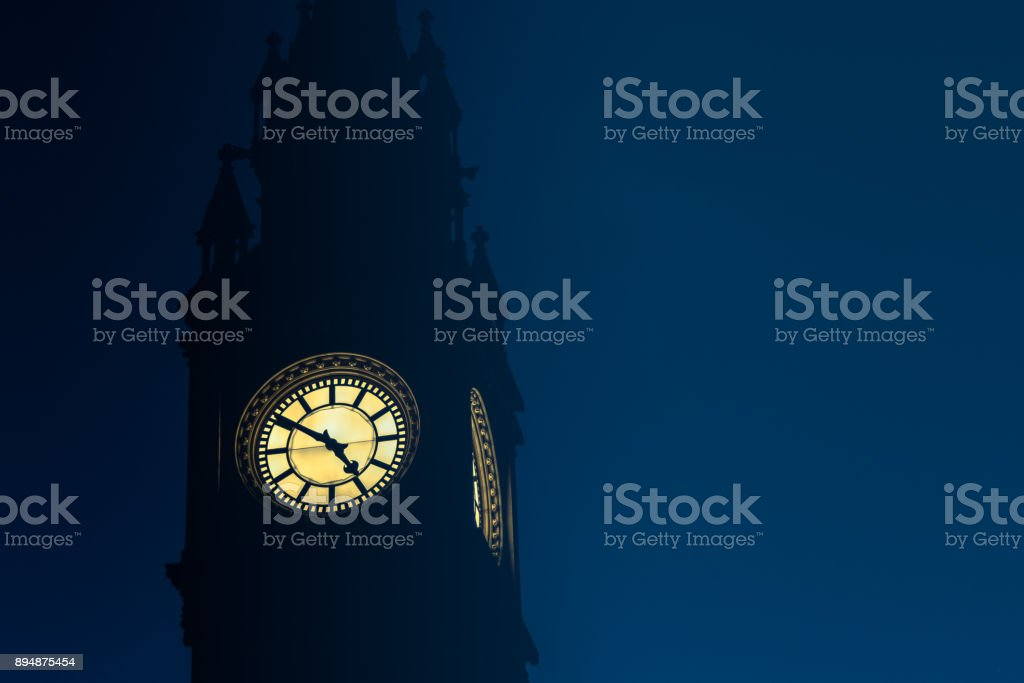 Clock face reading 4.50pm against dusk sky stock photo