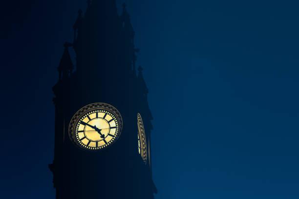 Clock face reading 4.50pm against dusk sky stock photo