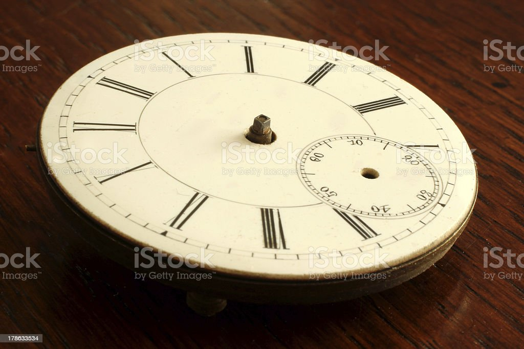 Clock face watch no hands scrimshaw roman numerals wooden table royalty-free stock photo
