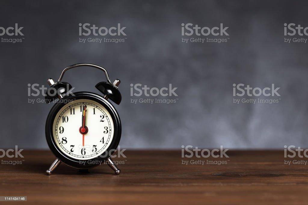 Clock hand at 12 o\'clock alarm at 5 o\'clock. Vintage / retro black...