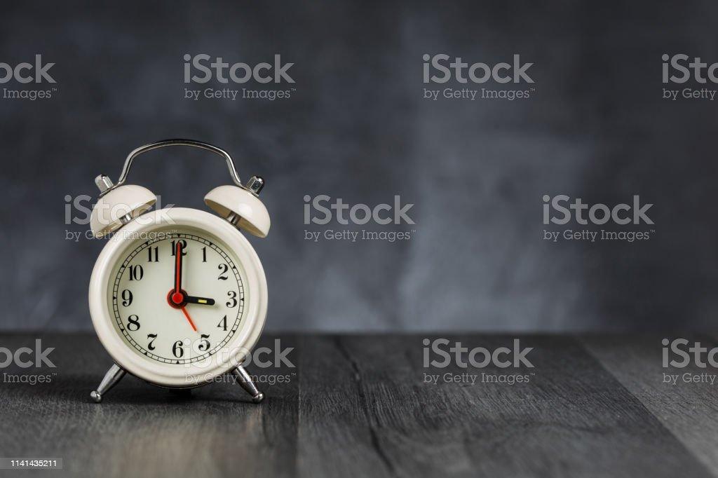 Clock hand at 3 o\'clock alarm at 5 o\'clock. Vintage / retro white...