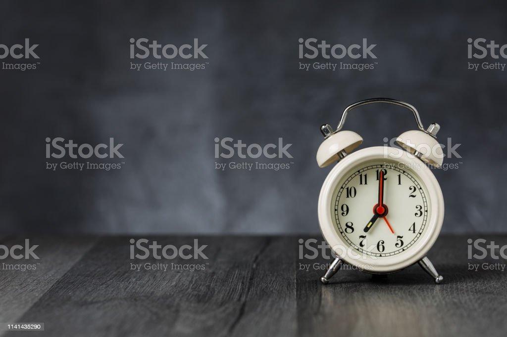 Clock hand at 7 o\'clock alarm at 5 o\'clock. Vintage / retro white...