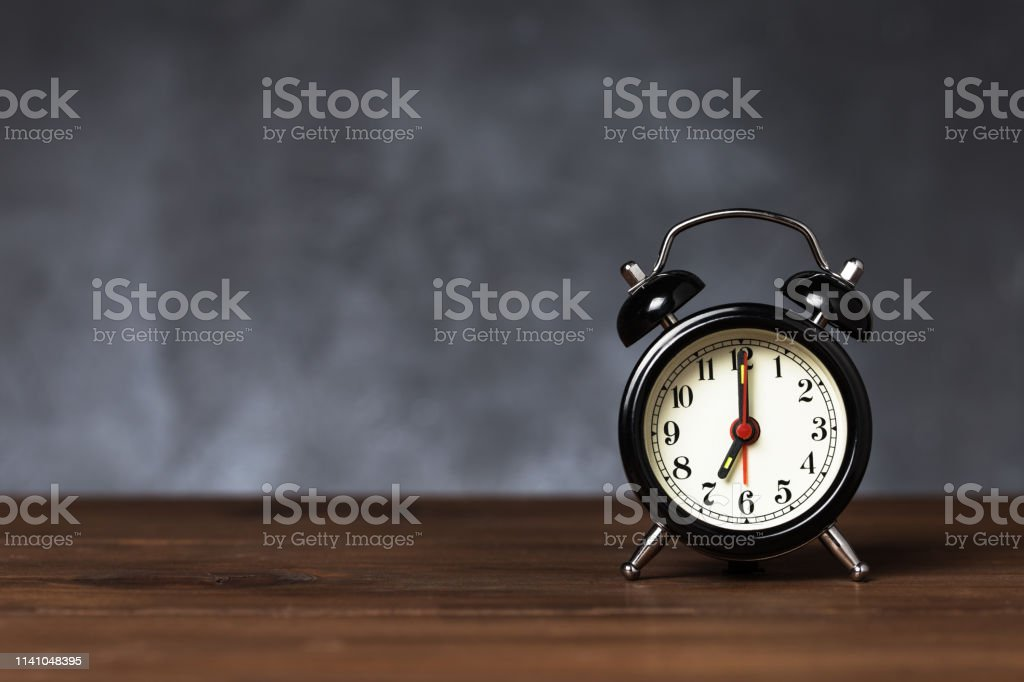 Clock hand at 7 o\'clock alarm at 6 o\'clock. Vintage / retro black...