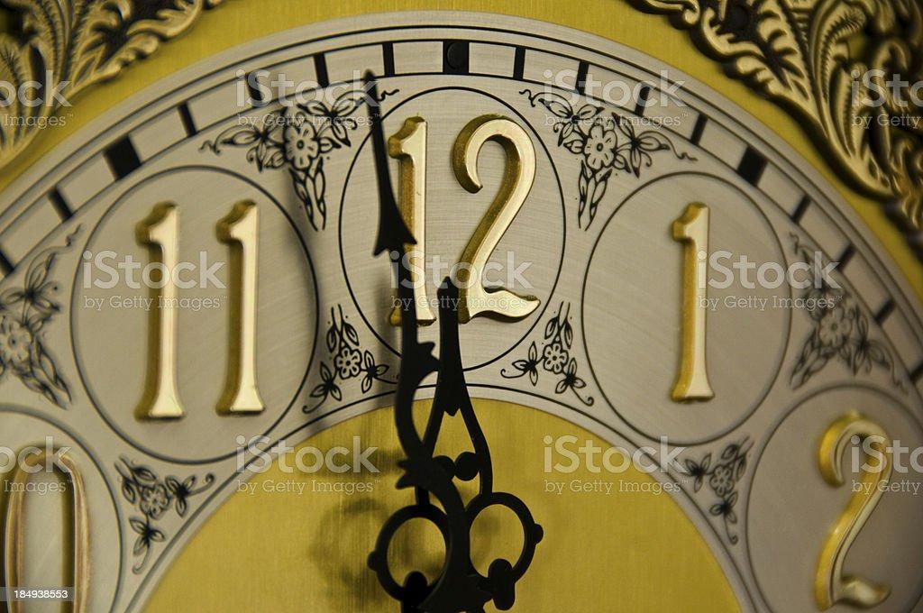 Closeup of clock hands on an ornate clock approaching 12 o\'clock.