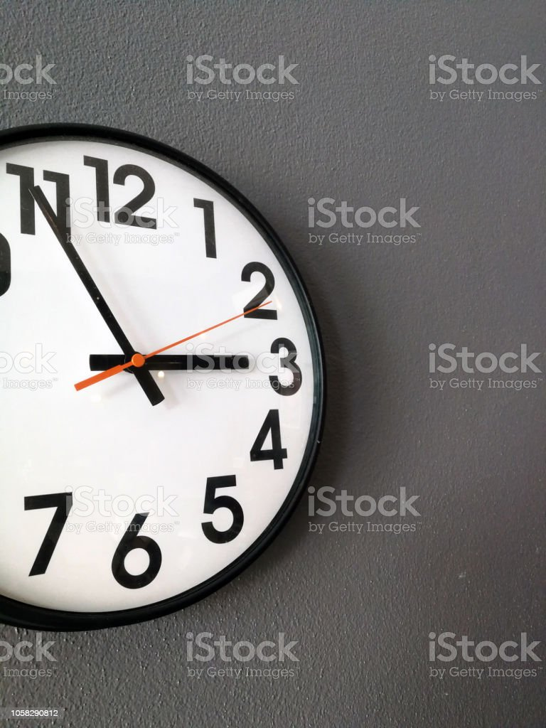 Clock hanging at the wall stock photo