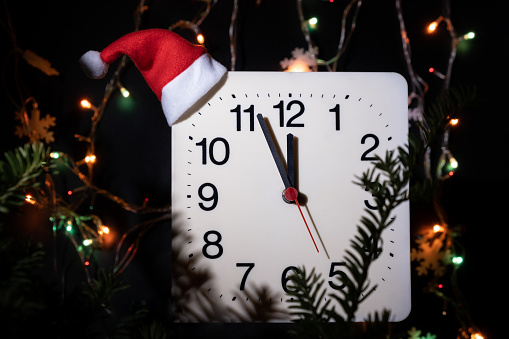 Clock in branches of New Year's fir on black background. Second hand moves in circle of mechanical clock and show Twelve o'clock at  Midnight and eve of Christmas. Holiday concept, time lapse, closeup, close-up