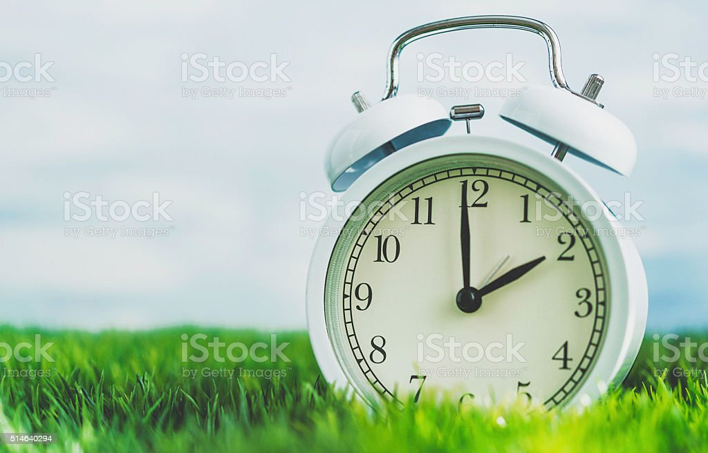 Clock in grass conceptualizing start of spring and DST stock photo