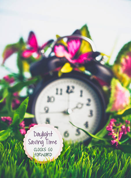 Clock in grass with spring foliage daylight savings time reminder picture id513064744?b=1&k=6&m=513064744&s=612x612&w=0&h=upsttzca4fhkz24g685lksvpwy4ge kybb d4ax64oo=