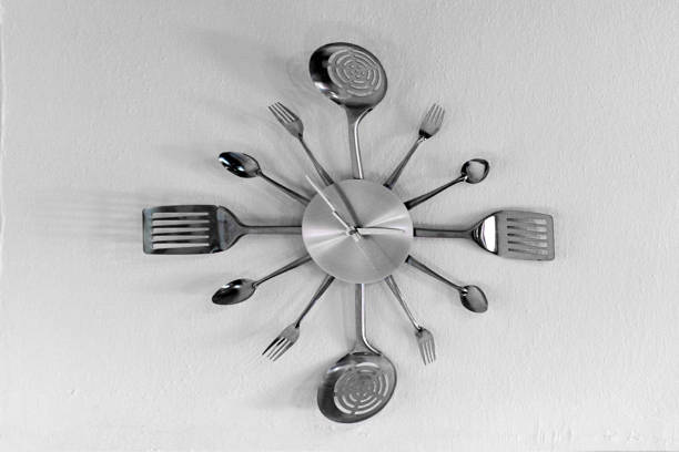 Clock made of spoons and forks on the wall stock photo