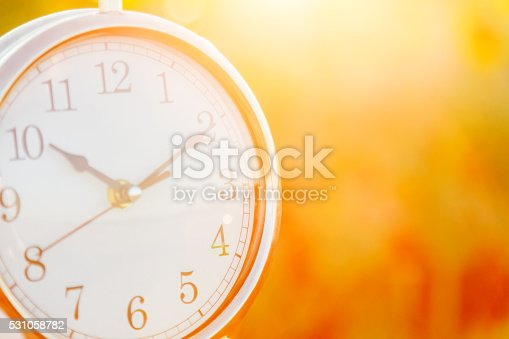 istock Clock on a sunset background close up 531058782