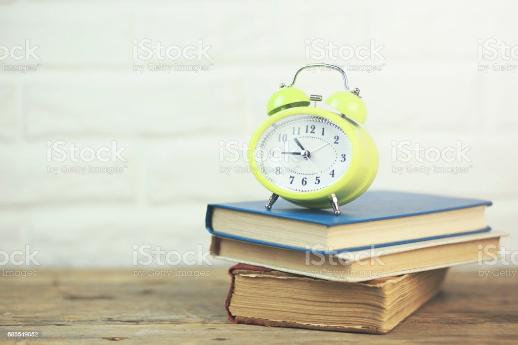 clock on books stock photo