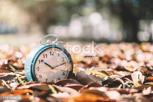 Clock on dry leaves with bokeh sun light abstract background. Copy space of time and life concept. Vintage tone filter effect color style.