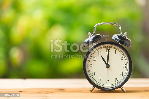 clock on wood table in the green garden time at 11 o'clock