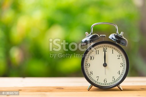 clock on wood table in the green garden time at 12 o'clock