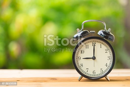clock on wood table in the green garden time at 9 o'clock