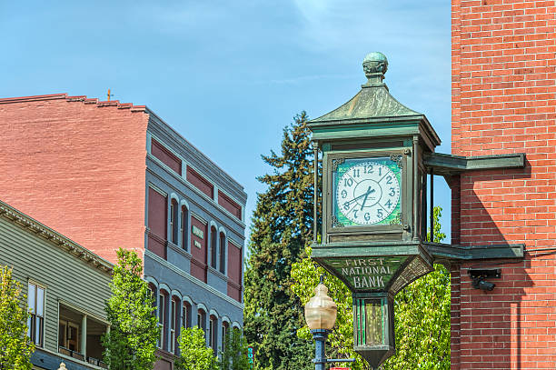 Clock on Historical Bank Building Hood River, Oregon, USA- April 18, 2014: Old verdigris and stainglass clock on outside of the Historical First National Bank Building in Hood River, Oregon hood river valley stock pictures, royalty-free photos & images
