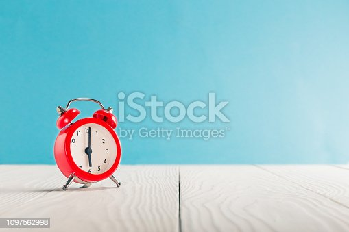 1048940572 istock photo Clock on light wooden table with colorful background. Time for wake up. 1097562998