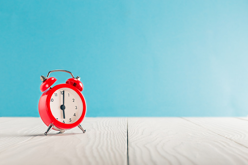 istock Clock on light wooden table with colorful background. Time for wake up. 1097562998