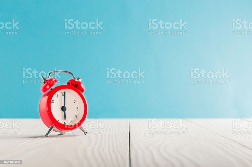 Clock on light wooden table with colorful background. Time for wake up. stock photo