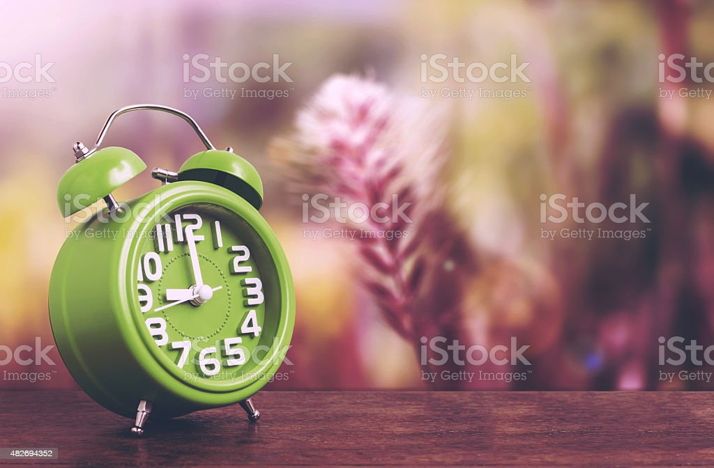 Clock on Wooden Floor with Flower Grass Background stock photo