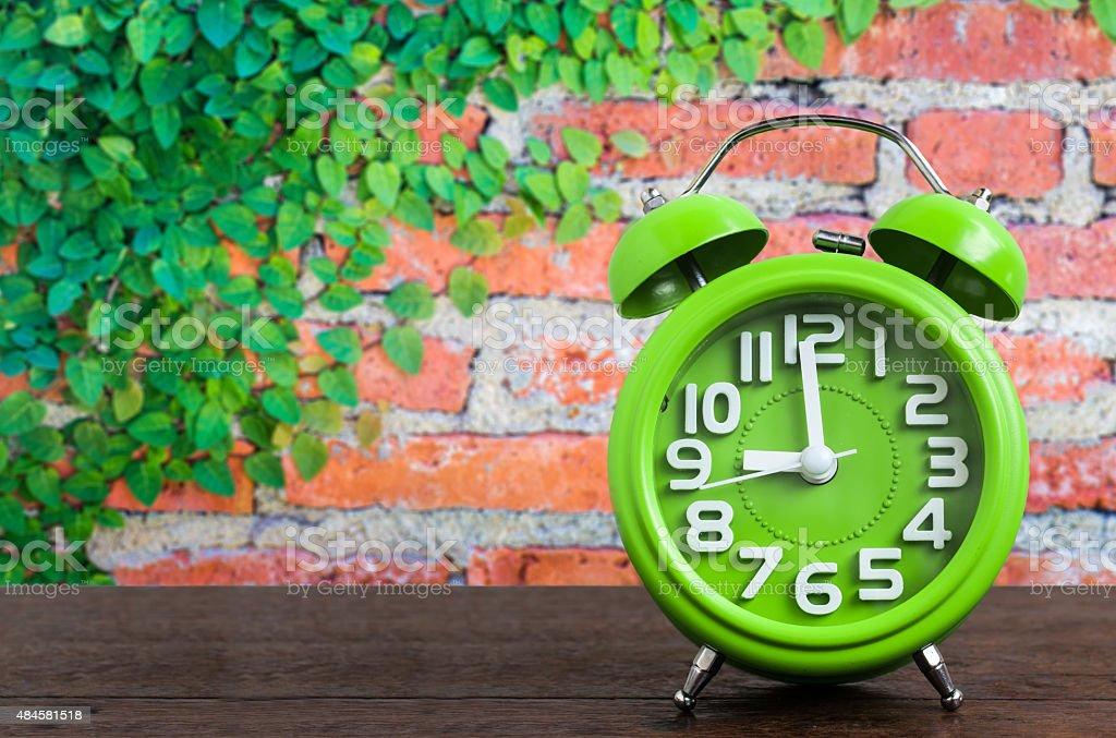Clock auf dem Holzboden, mit Pflanzen und Ziegel Wand Hintergrund – Foto