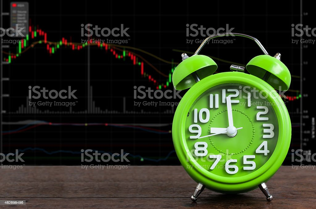 Clock on Wooden Floor with Stock Graph Background stock photo
