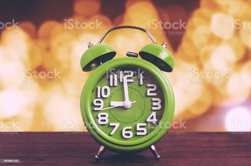 Clock on Wooden Floor with Yellow Bokeh Background stock photo
