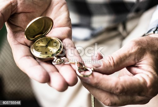 Old hands hold an antique pocket watch