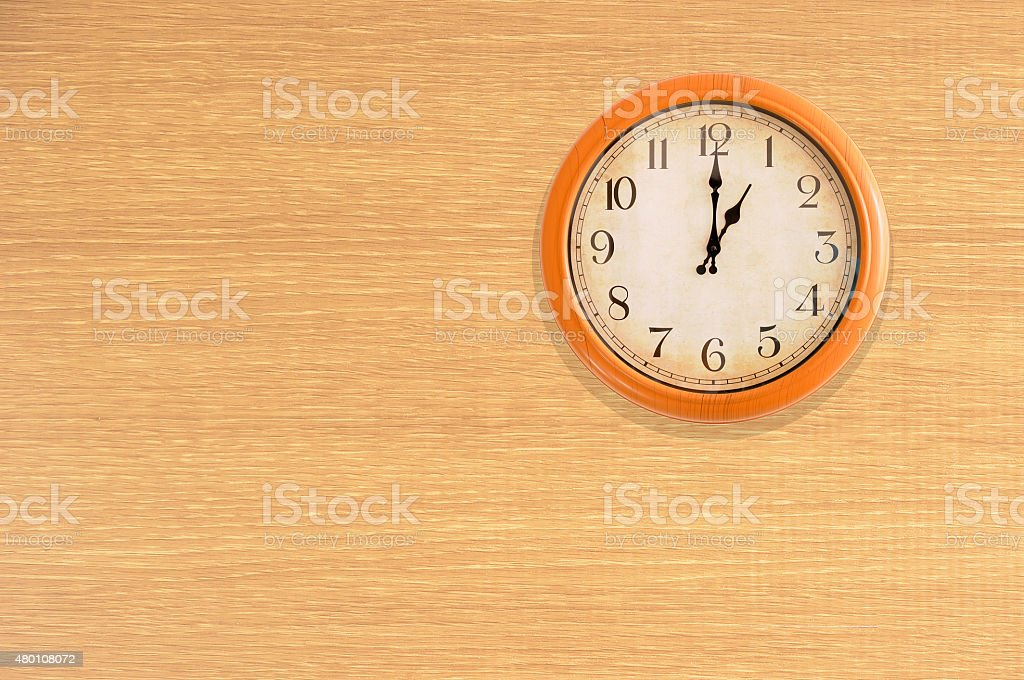 Clock showing 1 o'clock on a wooden wall stock photo