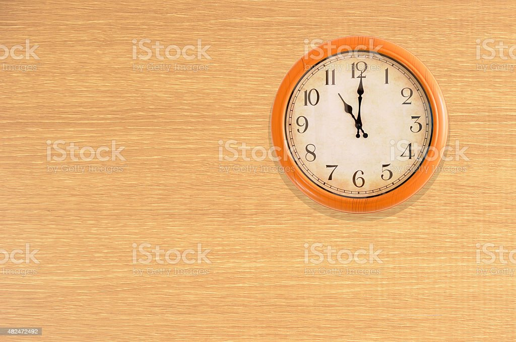 Clock showing 11 o'clock on a wooden wall stock photo