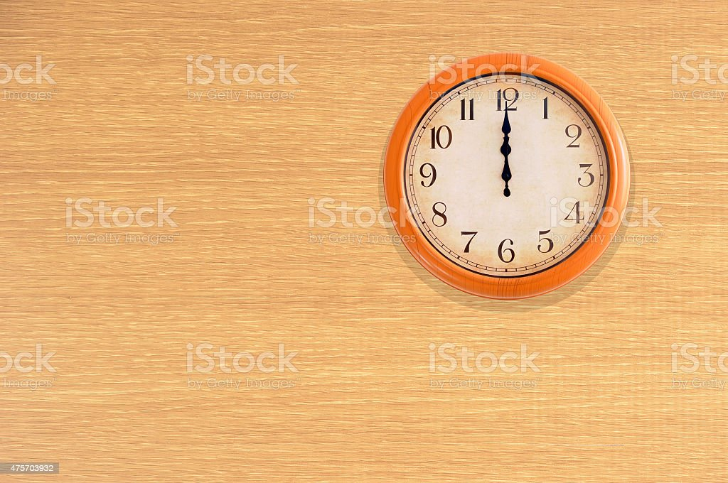 Clock showing 12 o'clock on a wooden wall stock photo