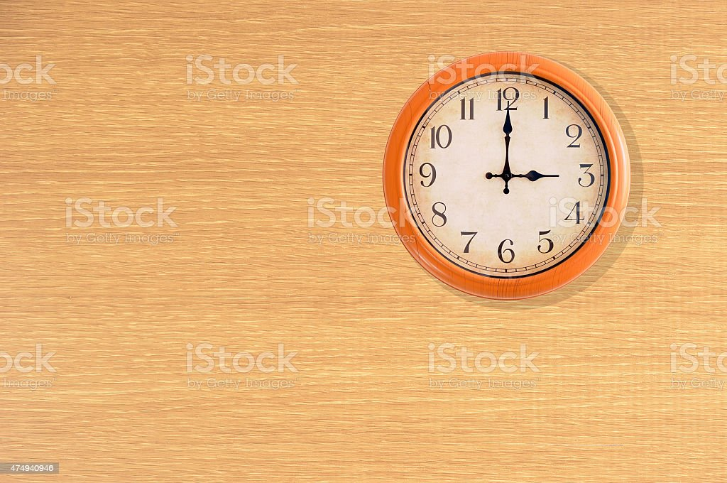 Clock showing 3 o'clock on a wooden wall stock photo