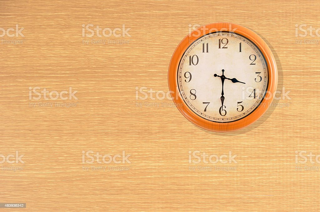 Clock showing 3:30 o'clock on a wooden wall stock photo