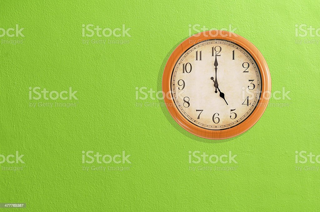 Clock showing 5:00 o'clock on a green wall royalty-free stock photo