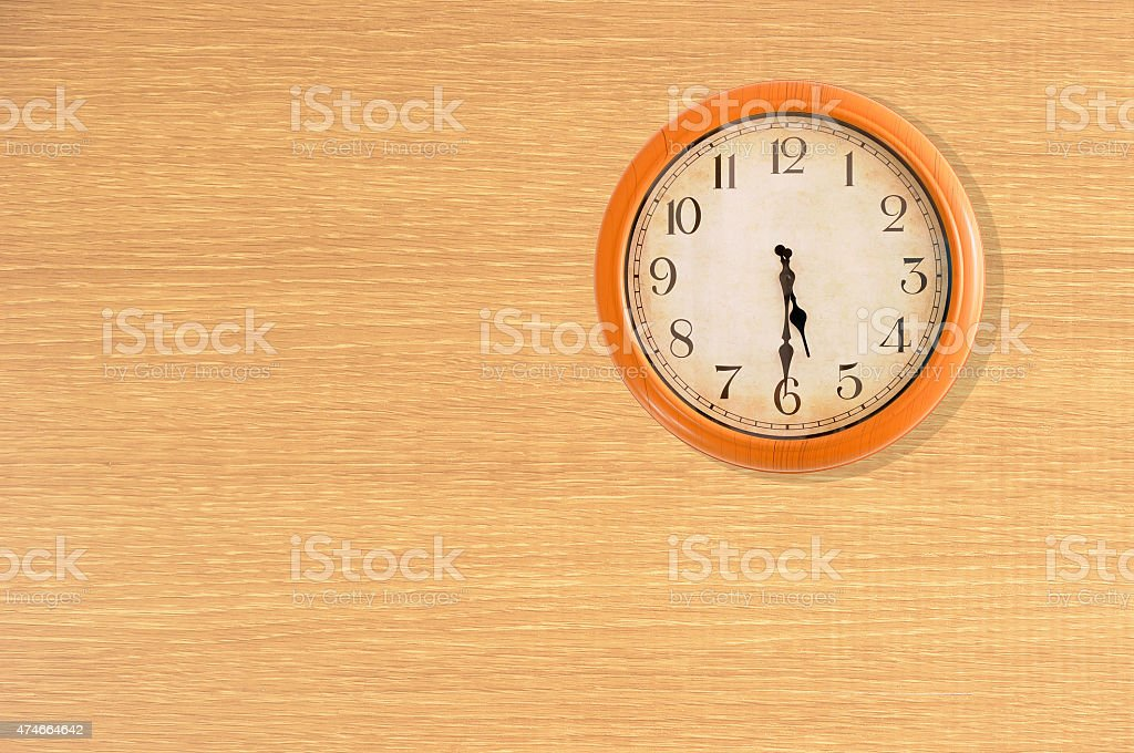 Clock showing 5:30 o'clock on a wooden wall stock photo