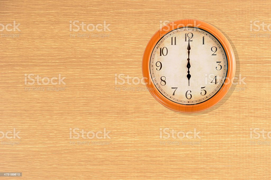 Clock showing 6 o'clock on a wooden wall stock photo